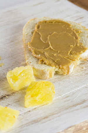 sugared: Closeup of peanut butter and a pieces of sugared pineapple on a wood. Stock Photo