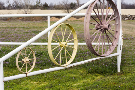 Gate with various sizes of wagon wheels.