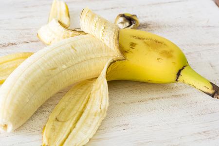 peeled banana: Closeup of peeled banana on a wood.