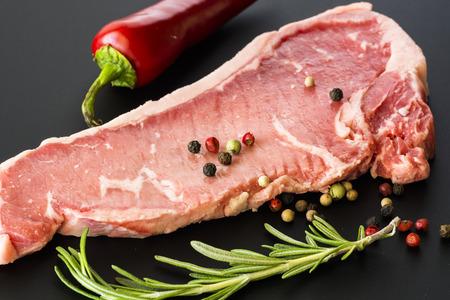 new york strip: Closeup of raw New York strip steak on a black background.