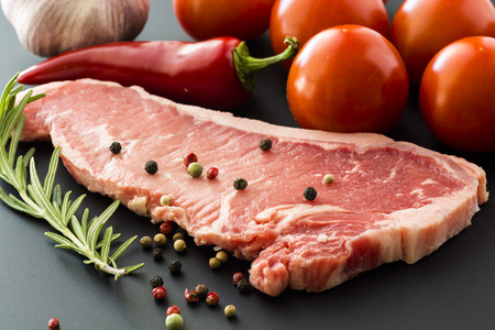 new york strip: Closeup of raw New York strip steak and tomatoes on a black background.