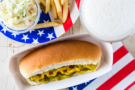 cole: Closeup of hot dog with mustard, relish, pickle and french fries, cole slaw,glass of beer on a table.