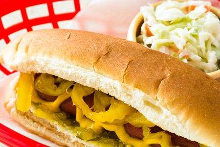 Closeup of hot dog with mustard, relish, pickle in a basket.