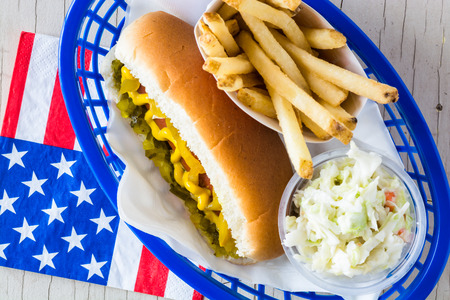 cole: Closeup of hot dog with mustard, relish, pickle and french fries, cole slaw in a basket.