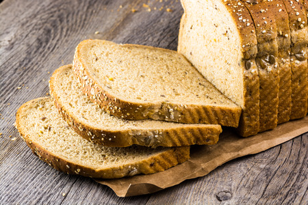 Close up of cut whole grain bread on a wood. Stock Photo