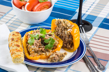 ground beef: Close up of roasted stuffed bell paper with ground beef and rice.