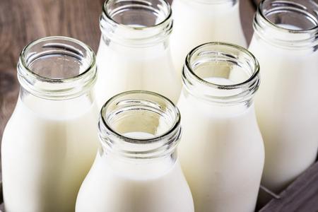 latte fresco: Primo piano di bottiglie di latte in una scatola di legno.
