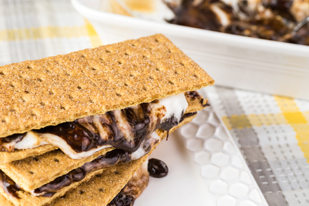 semisweet: Close up of smores with marshmallows and chocolate stacked on a plate.