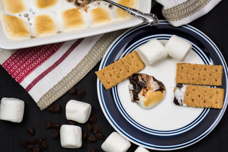 semisweet: Close up of fresh smores dip and crackers on a plate.