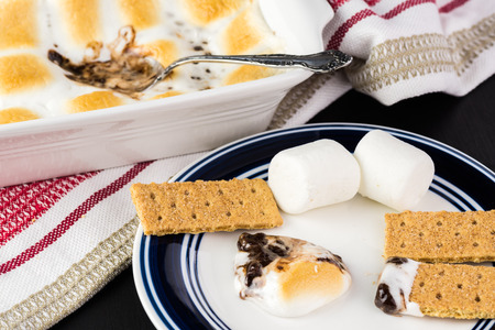 morsels: Close up of fresh smores dip and crackers on a plate.