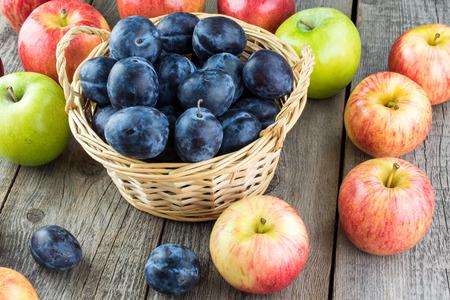 ciruela pasa: Cierre de ciruelas en una cesta y las manzanas en una madera.