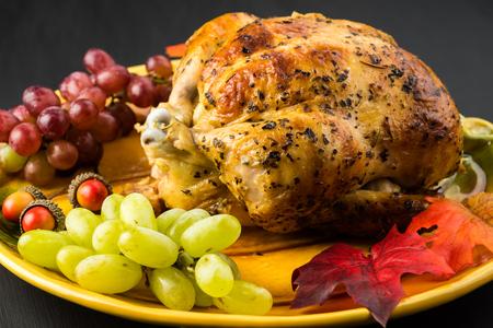 Close up of grilled whole chicken on thanksgiving dish with grapes and decoration stuff.