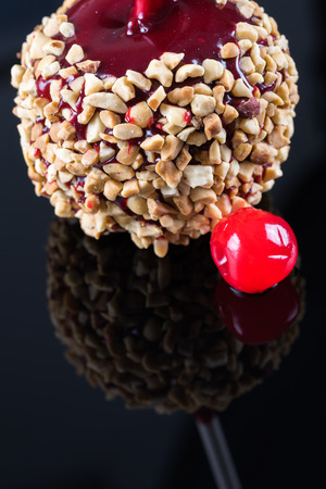 candy apple: Close up of candy apple with nuts on a black reflecting surface.