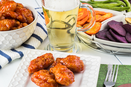 boneless: Close up of plate with boneless buffalo chicken wings, glass of beer on football season party table.