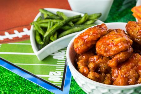 alitas de pollo: Cerca de la taza con las alas de pollo sin hueso de b�falo en la mesa de fiesta de la temporada de f�tbol.