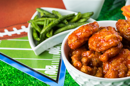 Close up of bowl with boneless buffalo chicken wings on football season party table.