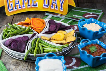 party food: Close up of assorted vegetable chips -  football season party vegetarian plate and assorted dips.