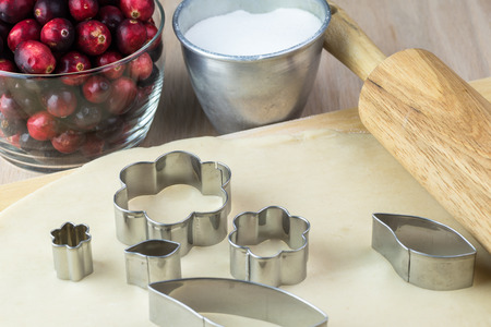 cookie cutter: Close up of roller, crust and metal cookie cutter for cranberry pie.