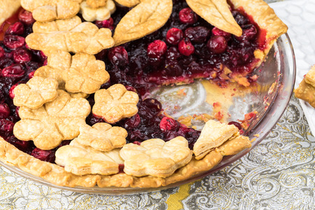 Close up of cut, homemade cranberry pie with crust flowers topping decoration. Imagens