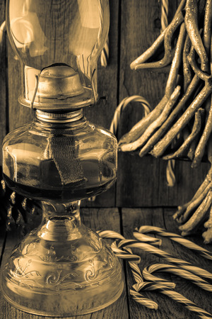 oil lamp: Close up of Christmas decoration with candy canes, old oil lamp. Stock Photo