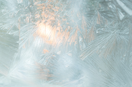 Close up of frosted window with Christmas light inside.