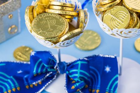 hanuka: Close up of chocolate Hanukkah gelt coins in vases.