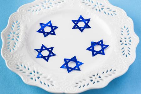 hanuka: Close up of white plate decorated with blue stars -  Hanukkah symbol on blue background. Stock Photo