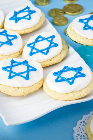 stelle blu: Close up of cookies decorated with blue stars -  Hanukkah symbol on a white tray.