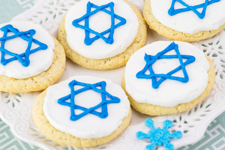 Close up of cookies decorated with blue stars -  Hanukkah symbol on a white plate.