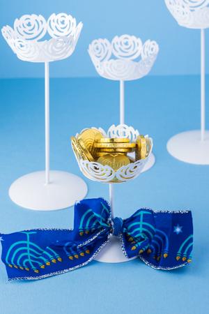 gelt: Close up of chocolate Hanukkah gelt coins in vase with Hanukkah bow. Stock Photo