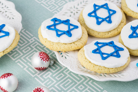 stelle blu: Close up of cookies decorated with blue stars -  Hanukkah symbol on a white plate.