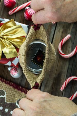 Close up of grandma hand closing the burlap bag with Christmas gift. 版權商用圖片
