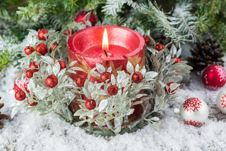 lit candle: Close up of Christmas ornaments, Christmas tree and lit candle in snow. Stock Photo