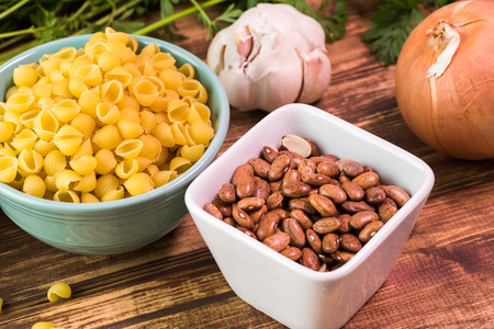 pinto beans: Close up of bowl with small pasta shells and pinto beans - ingredients for minestrone soup.
