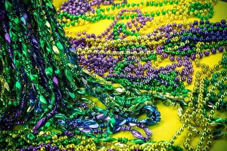 mardigras: Colorful mardigras beads on yellow background. Stock Photo