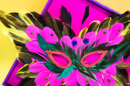 mardigras: Close up of mardigras mask in the pink box on yellow background.