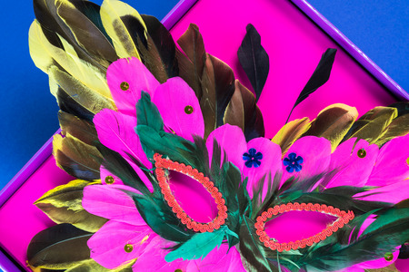 mardigras: Close up of mardigras mask in a pink box on the blue background. Stock Photo