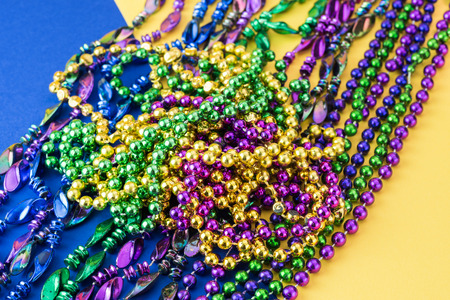 mardigras: Colorful mardigras beads on yellow and blue background.