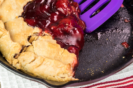 cherry pie: Close up of cut homemade cherry pie on iron skillet. Stock Photo