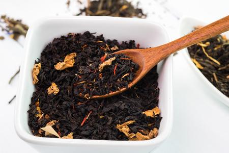 Close up der Tasse mit trockenen schwarzen Tee auf einem weißen Hintergrund.