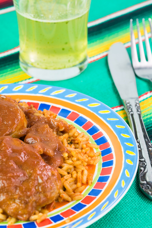 pork tenderloin: Close up of plate with pork tenderloin with adobo sauce and rice and glass of lime agua fresca Stock Photo
