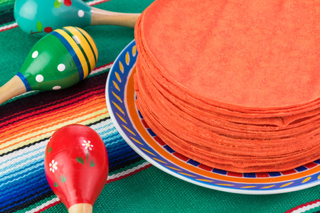 Close Up Of Stack Of Red Corn Tortillas On A Traditional Mexican Table  Runner. Stock