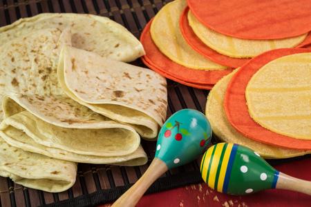 Close up of flour and corn tortillas and fiesta maracas. Stock Photo