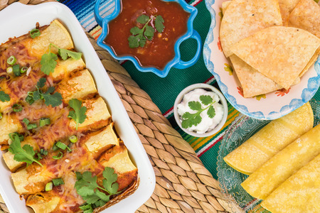 chips and salsa: Top view of traditional mexican food - enchiladas, salsa, chips, corn tortillas and sour cream on a colorful mexican table runner.