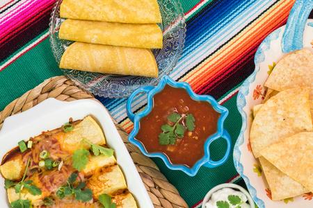 伝統的なメキシコ料理 - エンチラーダ、サルサ、チップ、トウモロコシのトルティーヤ、カラフルなメキシコ テーブル ランナーにサワー クリーム 写真素材