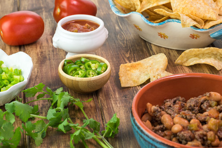 pinto beans: Close up of bowl with beef and pinto beans, chili pepper, tortilla chips -  ingredients for nachos. Stock Photo