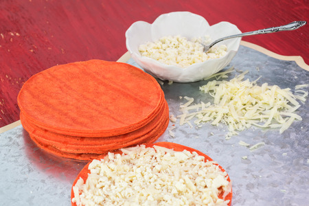 shredded cheese: Close up of cutting board with stack of red tortillas and shredded cheese on a wooden red background.