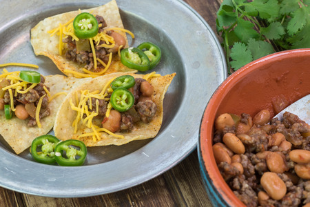 pinto beans: Close up of metal plate of nachos with beef and pinto beans and cheddar cheese on a wooden background.