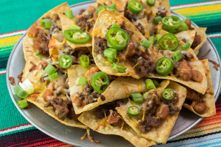 pinto beans: Close up of metal plate of cooked nachos with beef and pinto beans on a traditional mexican table runner.