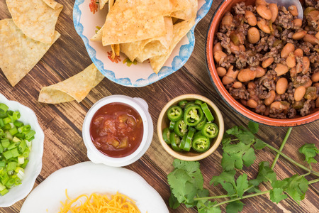 pinto beans: Top view of bowl with mixed beef and pinto beans, tortilla chips, salsa, cheese  - ingredients for nachos on a wooden background.